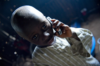 Young child listens on a mobile telephone | by World Bank Photo Collection