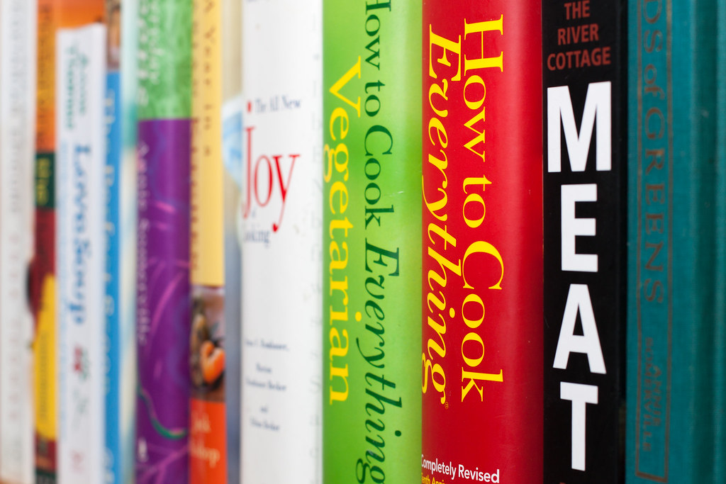 Close-up of cookbooks on a book shelf