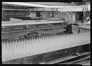 Numerous bottles in foreground and bottles on a conveyor belt, 1936 | by The U.S. National Archives