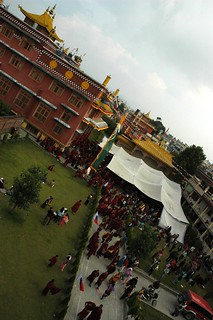 Sangha crowd departing on a rainy day from under the tent, newly installed prayer flags, Sakya Lamdre, Tharlam Monastery of Tibetan Buddhism, courtyard, as seen from the Tharlam Guesthouse, Boudha, Kathmandu, Nepal | by Wonderlane