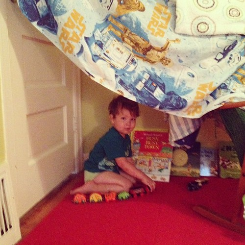 Very stoked about his fort stocked with books and trains | by Buster Benson