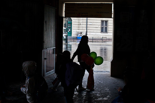 Green ballons, boy with jacket, a little hand and one food stand in the background | by javiermartinphoto