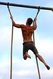 Man climbing rope as part of an intense workout. | by TerryGeorge.