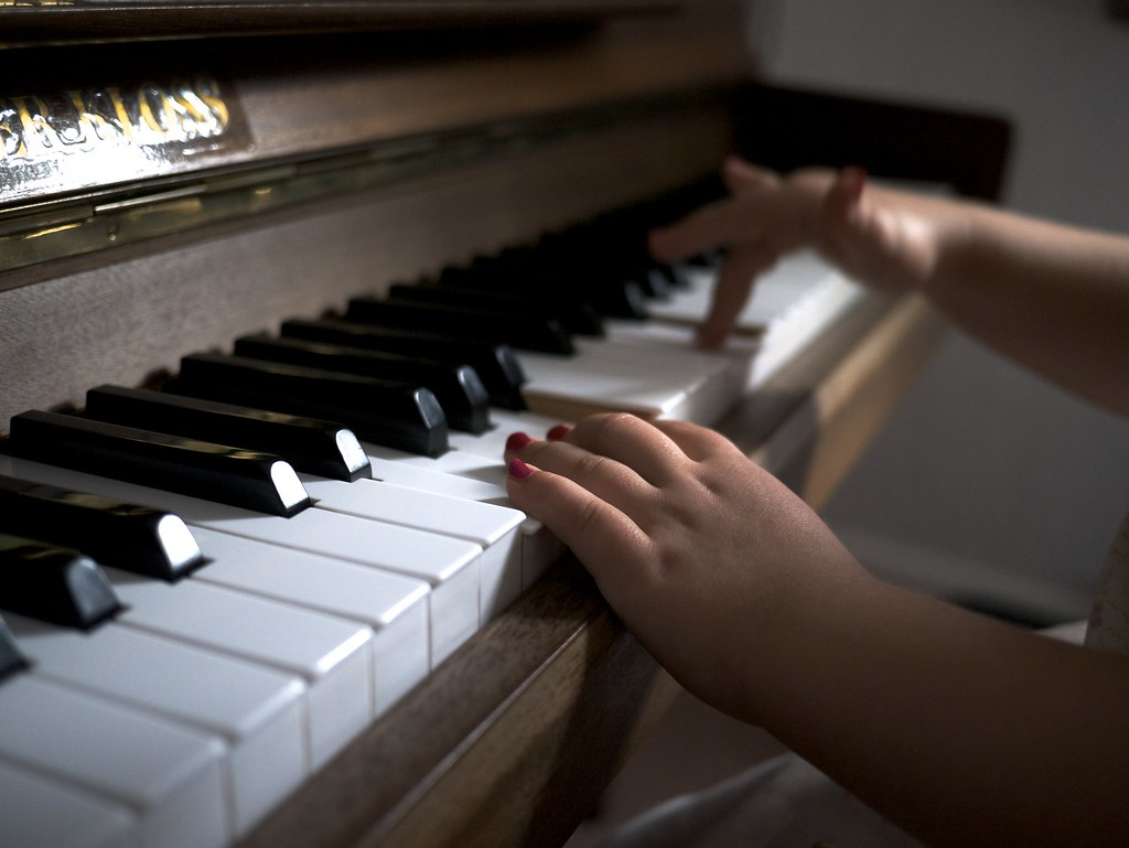 Young child playing the piano keys