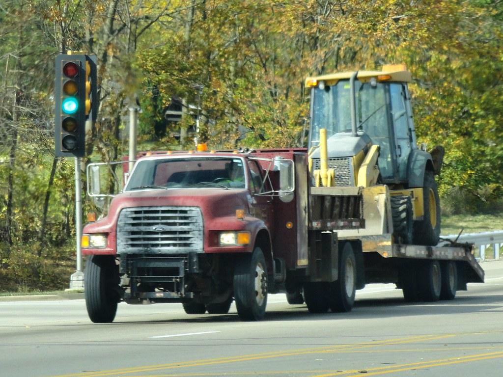 ford f750 dump truck hauling a backhoe