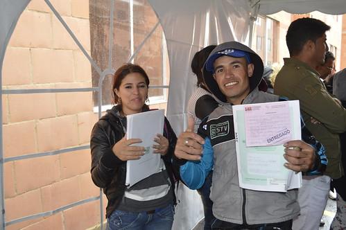 Fotografía de una mujer y un hombre mostrando documento de entrega de vivienda