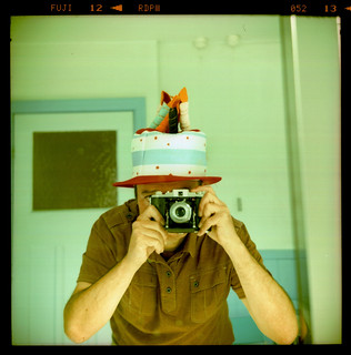 reflected self-portrait with Kodak 66 camera and novelty cake hat | by pho-Tony