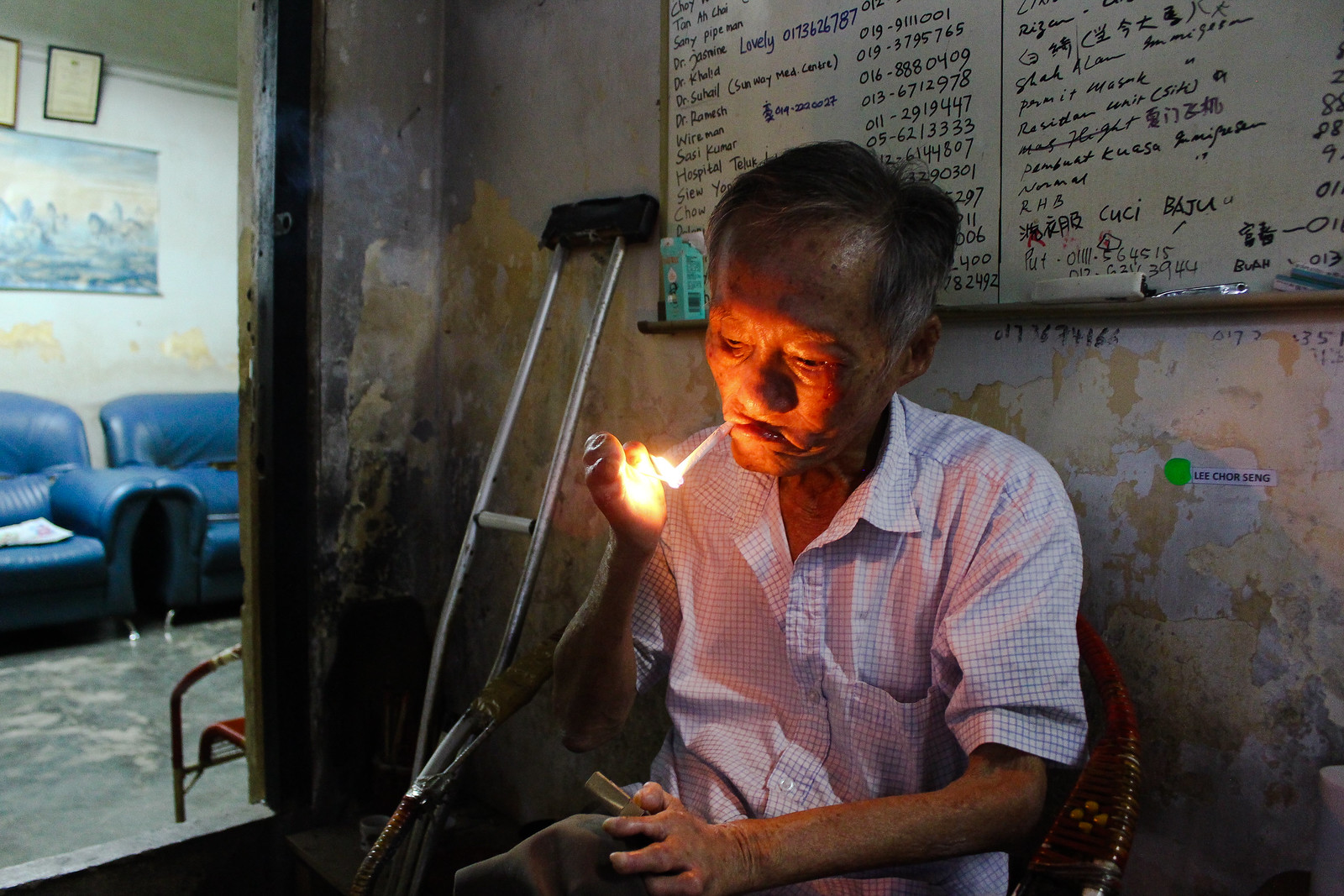在雙溪毛糯院已經住了將近一甲子的李初成,在家中熟練地點起一支菸,開始說故事。(攝影:何欣潔)