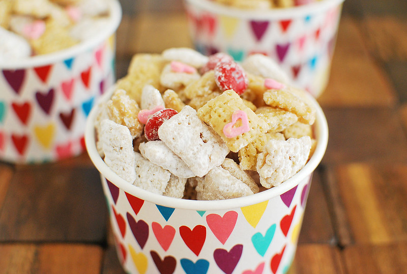 Cupid's Crunch - the cutest Valentine's Day treat! Chex cereal coated in white chocolate and peanut butter and tossed in powdered sugar. With Valentine's Day M&Ms and heart sprinkles!