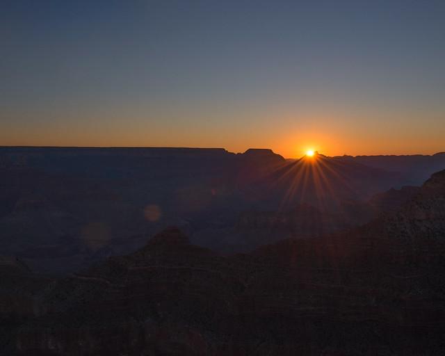 Rayos del sol asomando al amanecer entre los picos del Gran Cañón de Estados Unidos