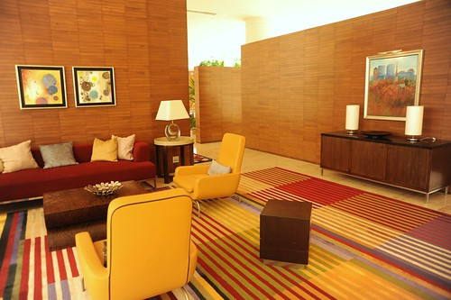 Lounge room, sofas, pillows, armchairs, end tables, lamps, art, sideboard, wood walls, striped carpet, red and yellow, contemporary furniture, Renaisance Hotel, Schaumburg, Illinois, USA | by Wonderlane