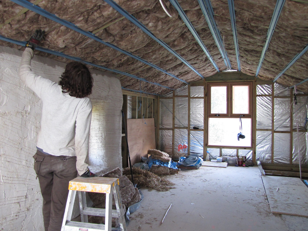 Sue installing insulation in attic roof strawbale house for New home insulation