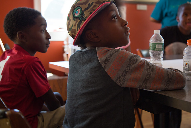 Zion Edwards, 11, left, and Tahlib Thomas, 8, listen closely to Writing Our Lives instructor Phil Haddix as he discusses their similar interest in video games. | Dominique Hildebrand,
