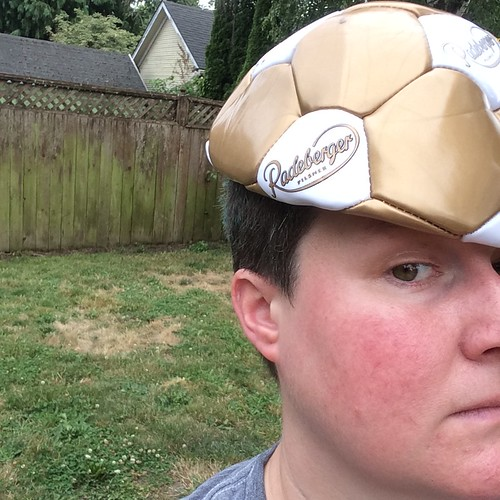 A very close up of my face with a gold and white, deflated soccer ball on my head like a hat.