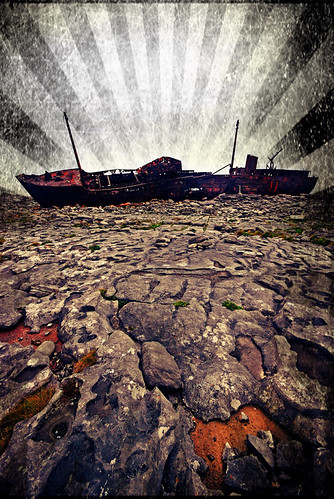 Rusted hulk of a ship wrecked on the rocks of Inisheer, the smallest of the Aran Islands off the wild Atlantic coast of Ireland done up in the photo app Pixlromatic