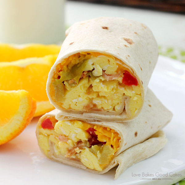 Bacon & Egg Breakfast Burritos on a white plate with orange wedges close up.