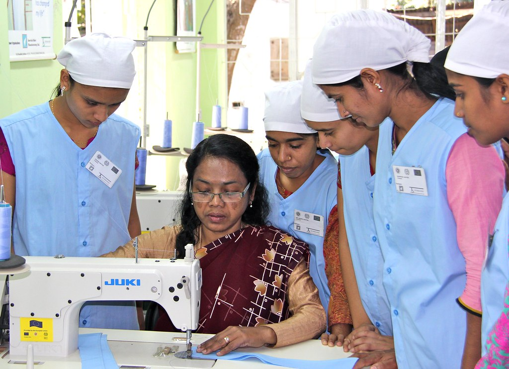 sewing machine operator trainees learning from instructor