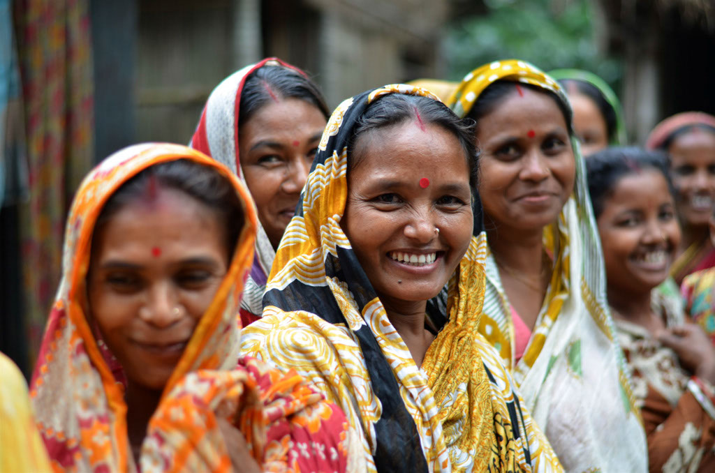 smiling farmers gathered during morning milk collection in