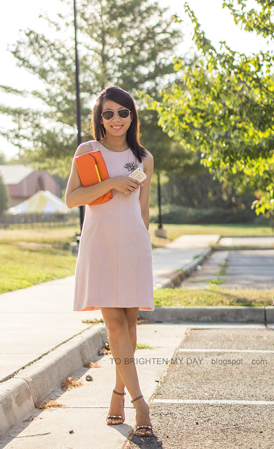 sparkly brooch pinned on pink wool shift dress, orange clutch, brown block heeled sandals