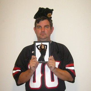 Portrait Of A Man In A Black Football Jersey With A Black Bear On His Head Holding A Picture Of A Hot Actress Wearing All Black | by pikespice
