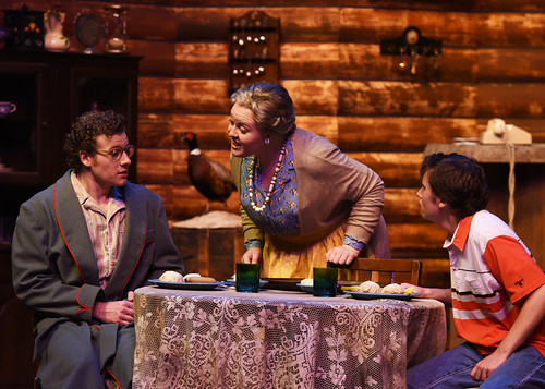 """Two actors sit at a table while an actress talks with them during the play """"The Foreigner."""""""