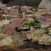 Pizza with mushroom, prosciutto, peas and pecorino cheese