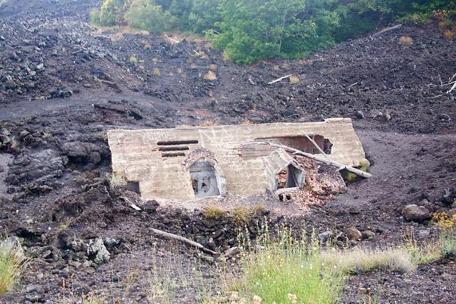 Wystający dach domu spod zastygniętej lawy na zboczu góry Etna