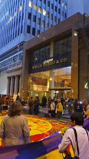 """SHAME"" projected on Wells Fargo as policeman inside videotapes rally from the second floor. 