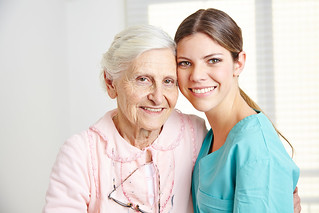 Smiling caregiver embracing happy senior woman in nursing home | by agilemktg1