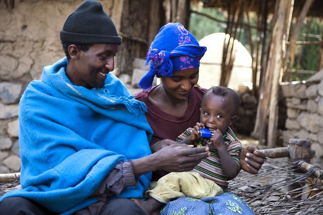 Model Farmer Wondossen and his son and sister outside their latrine in Romey Village-Amhara Region