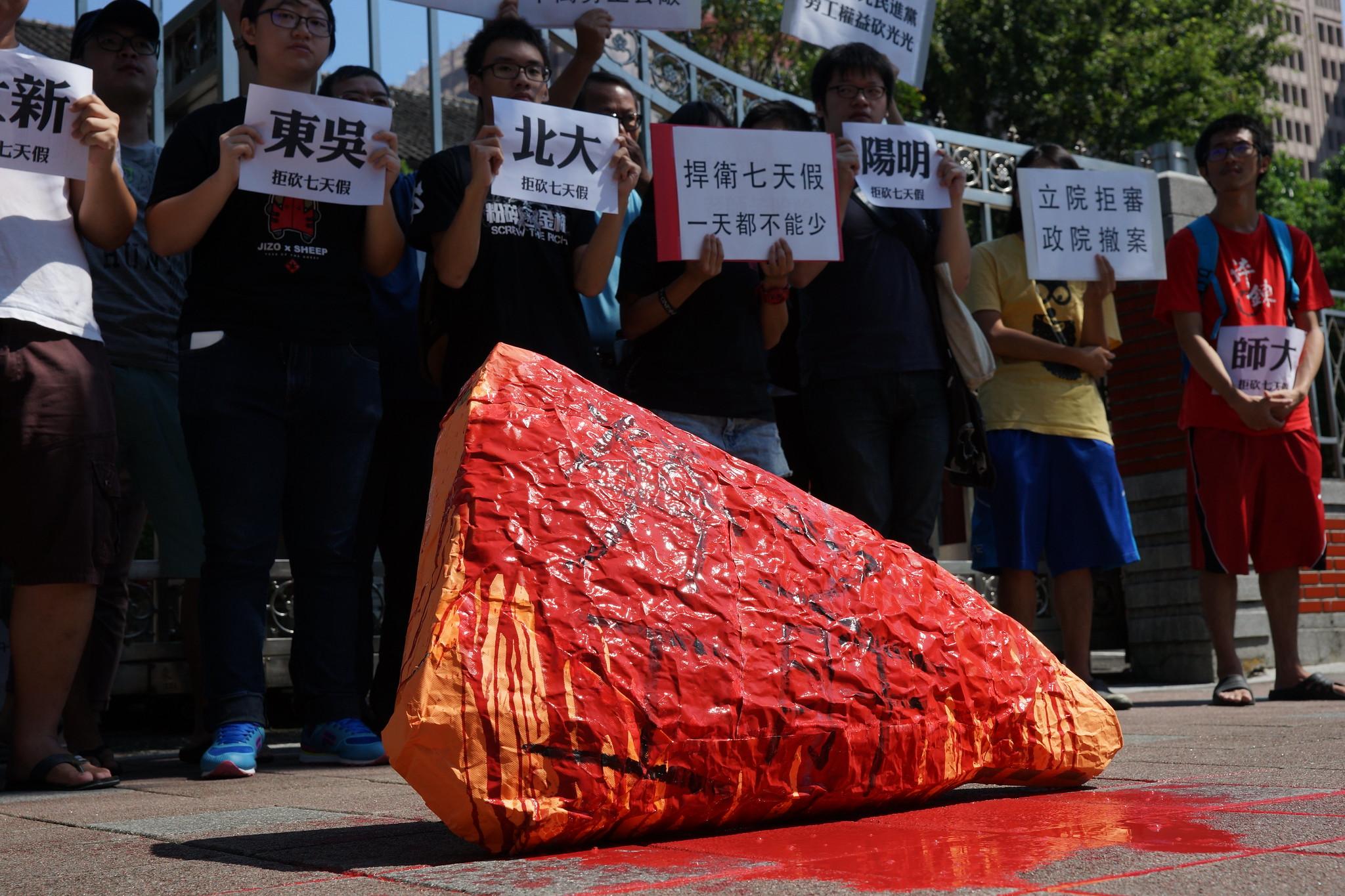 """各校学生打工族串连赴立院,送上淋有鲜血的""""劳工之肝"""",反对砍七天假。(摄影:王颢中)"""