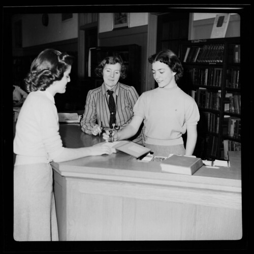 Miss Shirley Robbins works at a library reference desk, January 8, 1952 | by North Carolina Digital Heritage Center