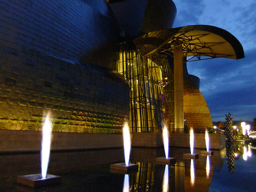 Fountains lit-up at night in front of Frank Gehry's architectural masterpiece, the Guggenheim modern art museum in Bilbao, Spain