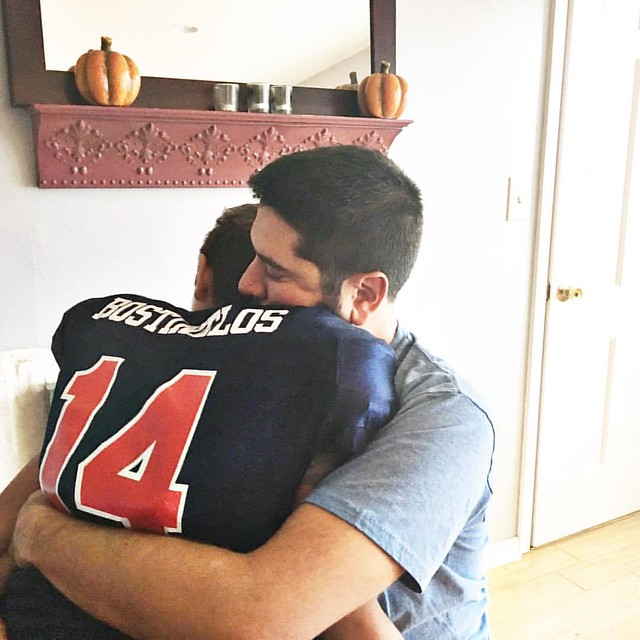 It's a divide and conquer type of day. Owen gets a big hug from @dimitri_bostinelos before we head out to his game. ❤️