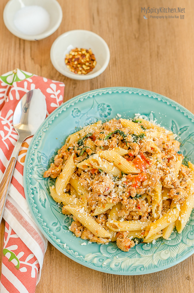 Penne Pasta with Hot Italian Sausage plated on a green plate