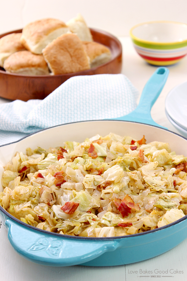 Southern Bacon-Fried Cabbage in a skillet with a bowl of bread rolls.