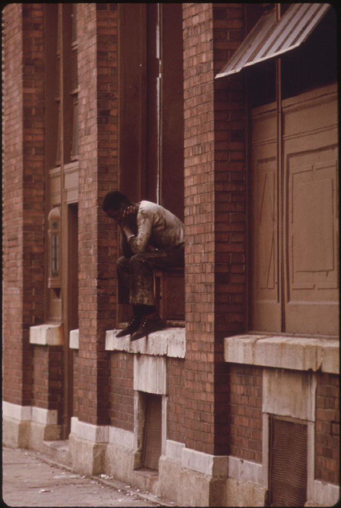 A Black Man Who is Jobless Sits on the Windowsill of a Building in a High Crime Area on Chicago's South Side, 07/1973 | by The U.S. National Archives