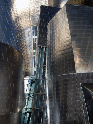 The metallic walls and curvilinear architectural design by Frank Gehry for the Guggenheim Modern Art Museum in Bilbao, Spain