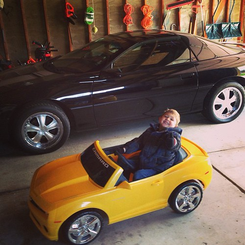 Vito posing in his yellow Camaro power wheels in front of ...