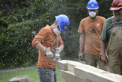 A Northern Bedrock Historic Preservation Conservation Corps crew member completing initial shaping on a sill log