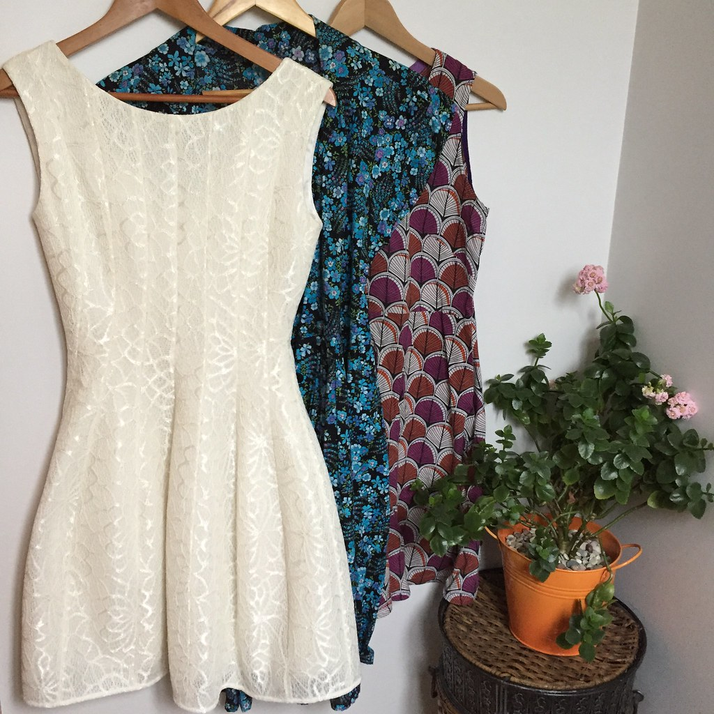 three long-worn dresses from my wardrobe, a white wedding dress, a blue and black floral button up dress and a purple, orange and white cotton shift dress