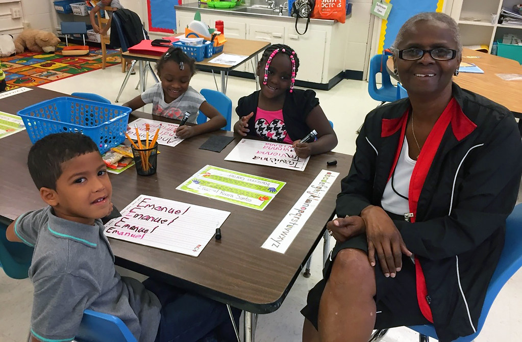 Foster Grandparent Volunteer with 3 kids in school setting