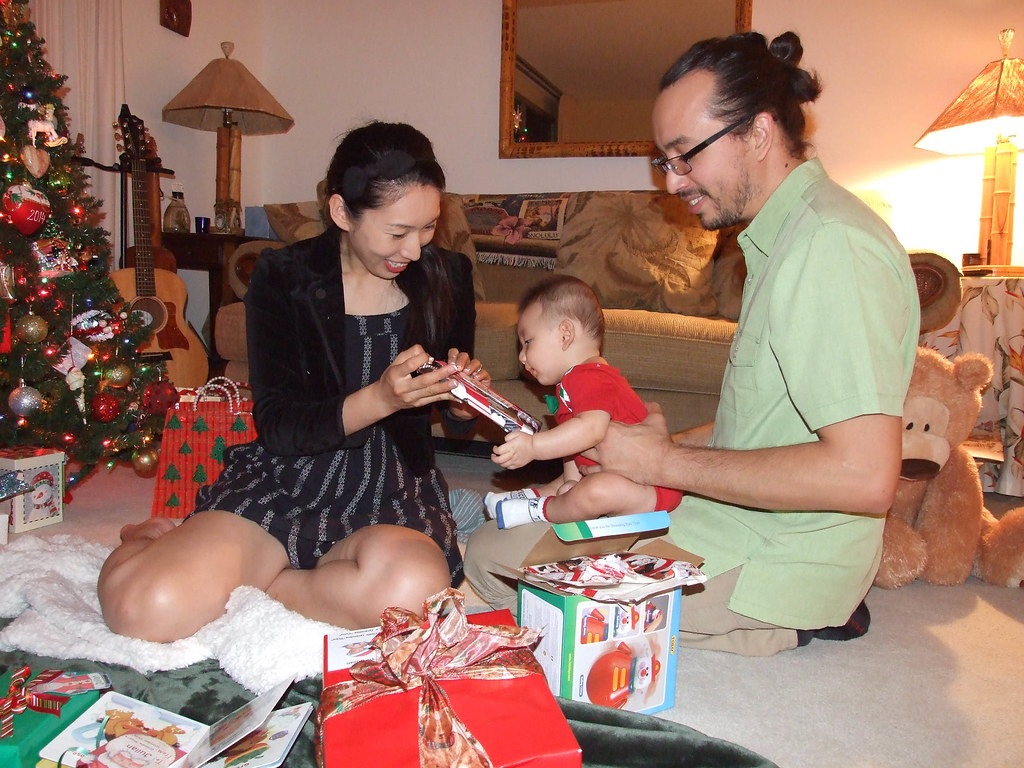 by new parents enjoy watching their baby open christmas gifts for the first time by