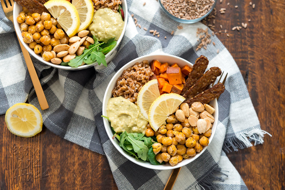 Two vegan fall farro protein bowls filled with almonds, farro, hummus, arugula, roasted chickpeas, tempeh bacon, and sweet potatoes