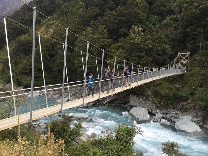 hiking in mount aspiring national park with swing bridge of the matukituki river