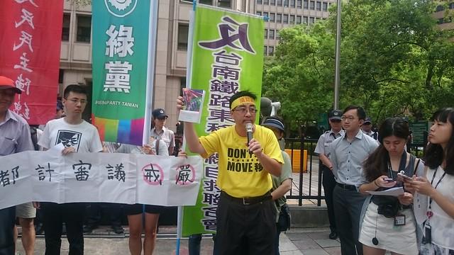 拿出內政部長葉俊榮上任前的著作,南鐵自救會要求先舉行聽證會。攝影:賴品瑀。