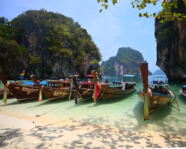 Barcas amarradas en la orilla de Koh Lading a la sombra de los árboles