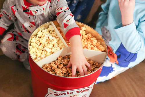 Child wearing pajamas with hand in holiday popcorn tin wth caramel, cheese and classic flavors | by PersonalCreations.com