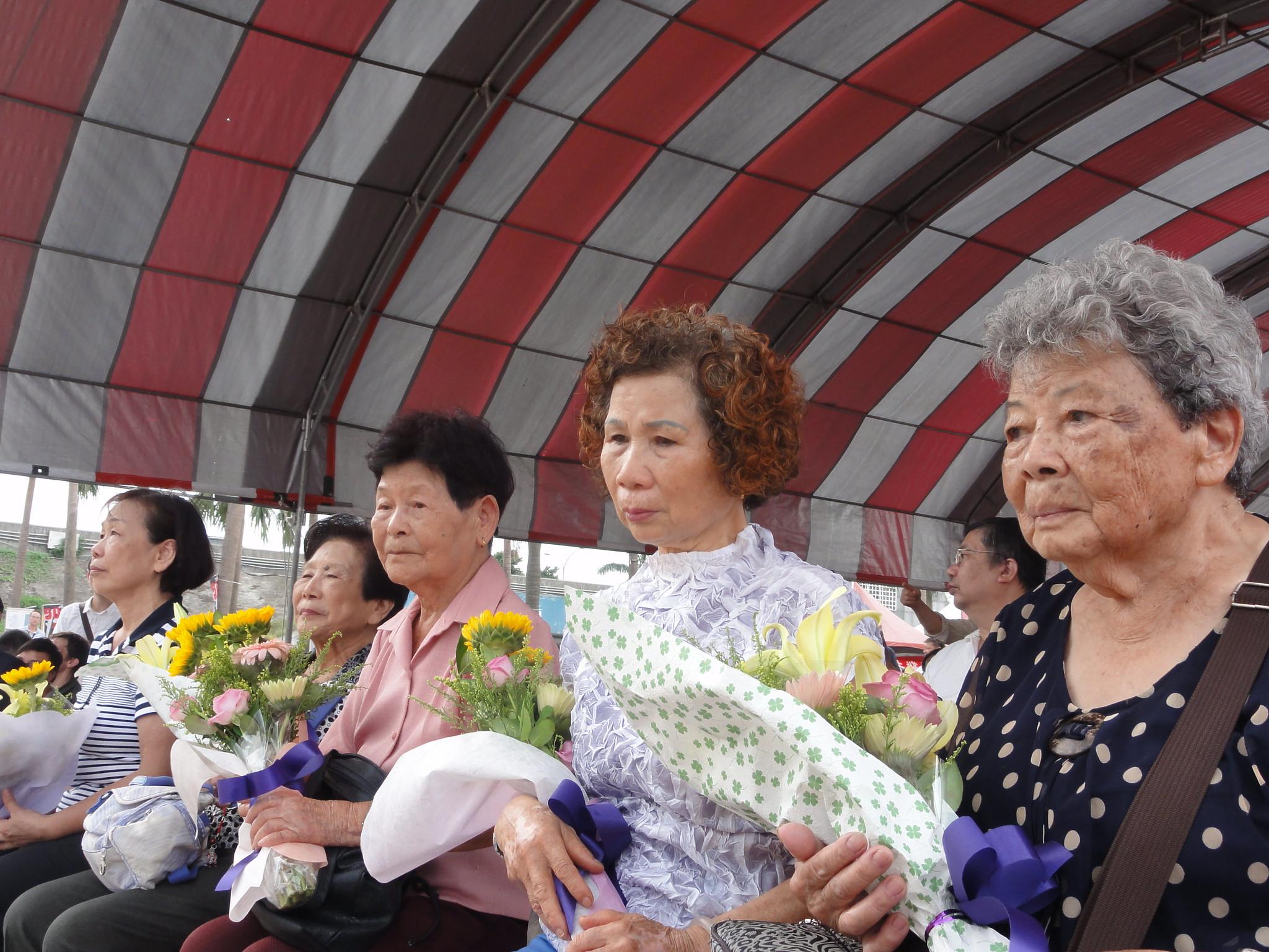 受難者遺族與家屬在追思會上接受鮮花致贈。(攝影:張智琦)