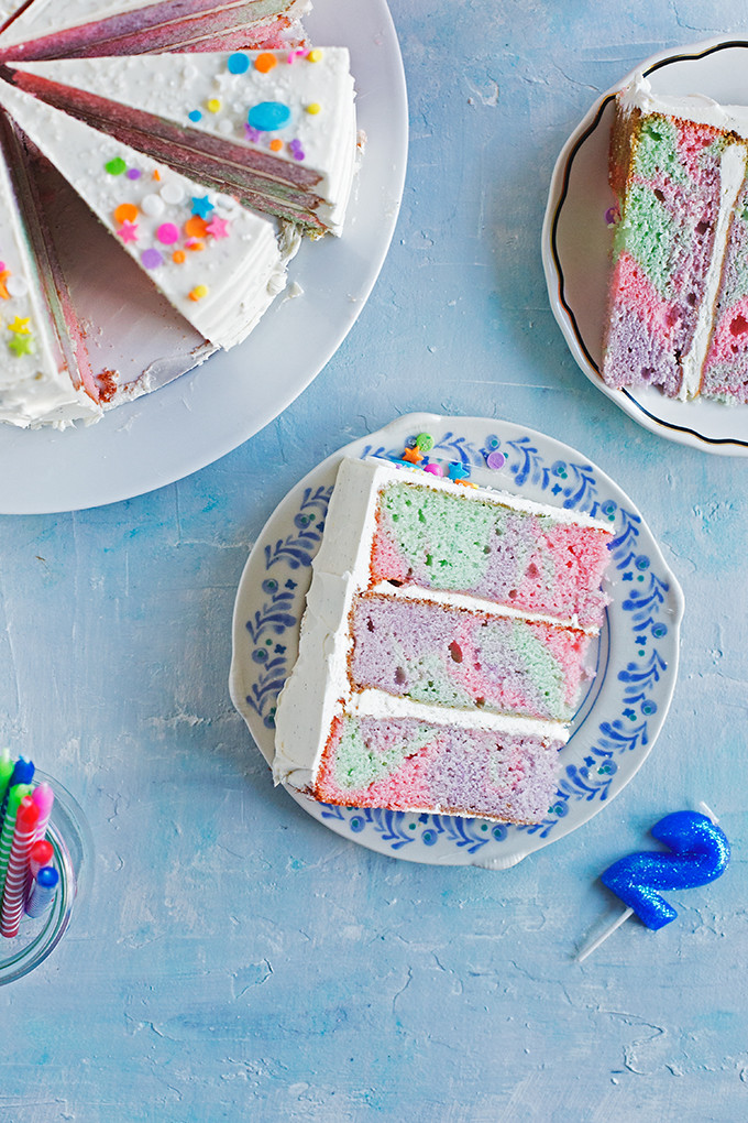Rainbow Marble Layer Cake - A festive cake with rainbow marbled vanilla bean + buttermilk cake layers frosted with swirls of silky vanilla bean swiss meringue buttercream.
